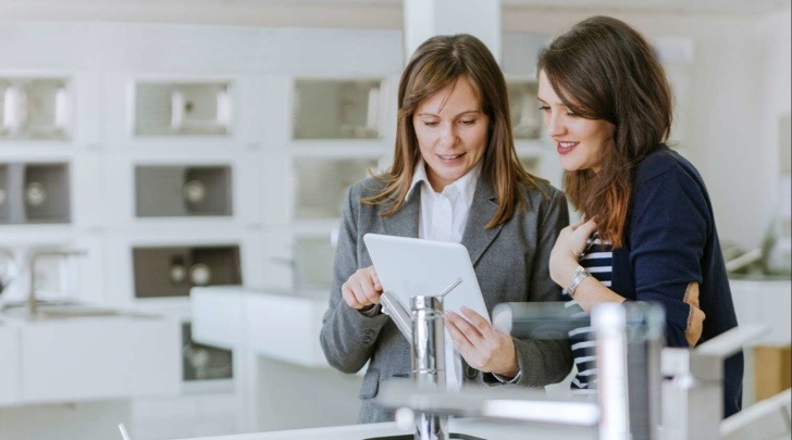 sales woman helping client in a kitchen retailer with a 3D planning solution on a tablet