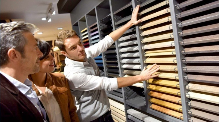 salesman in a kitchen retail store showcasing flooring options to a couple