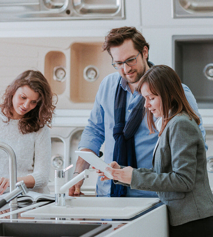 saleswoman with tablet consulting couple in a kitchen and bath store