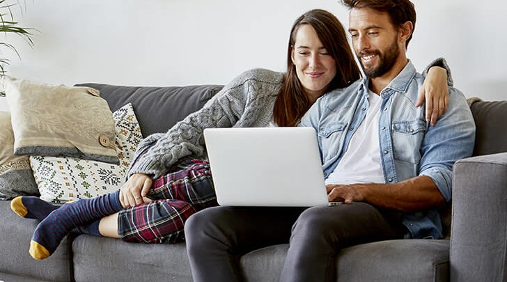 couple sharing a laptop in their living room