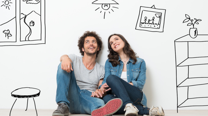 young couple daydreaming with cartoon images of new home