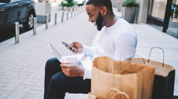 man designing on laptop while completing his purchase journey using his smartphone