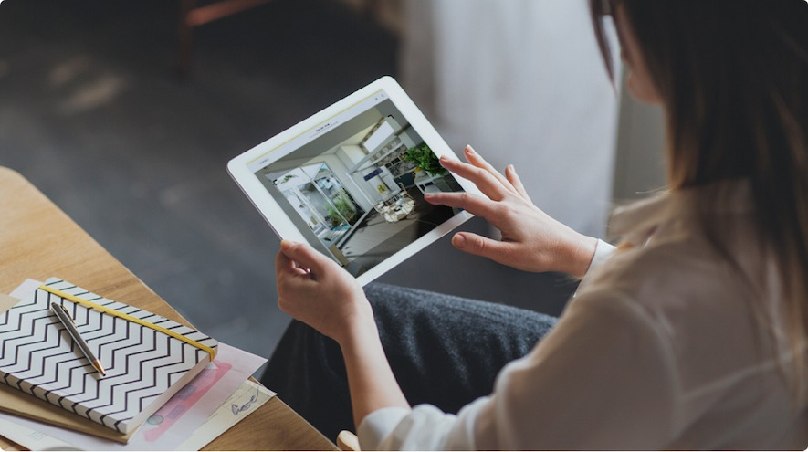 A woman using HomeByme on her tablet. She is taking a realistic image
